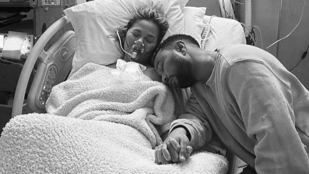 Chrissy Teigen y John Legend tomados de la mano y descansando en su habitación del hospital