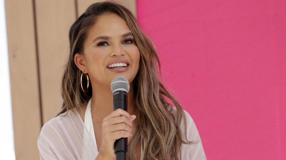 Chrissy Teigen sonriendo mientras habla por un micrófono