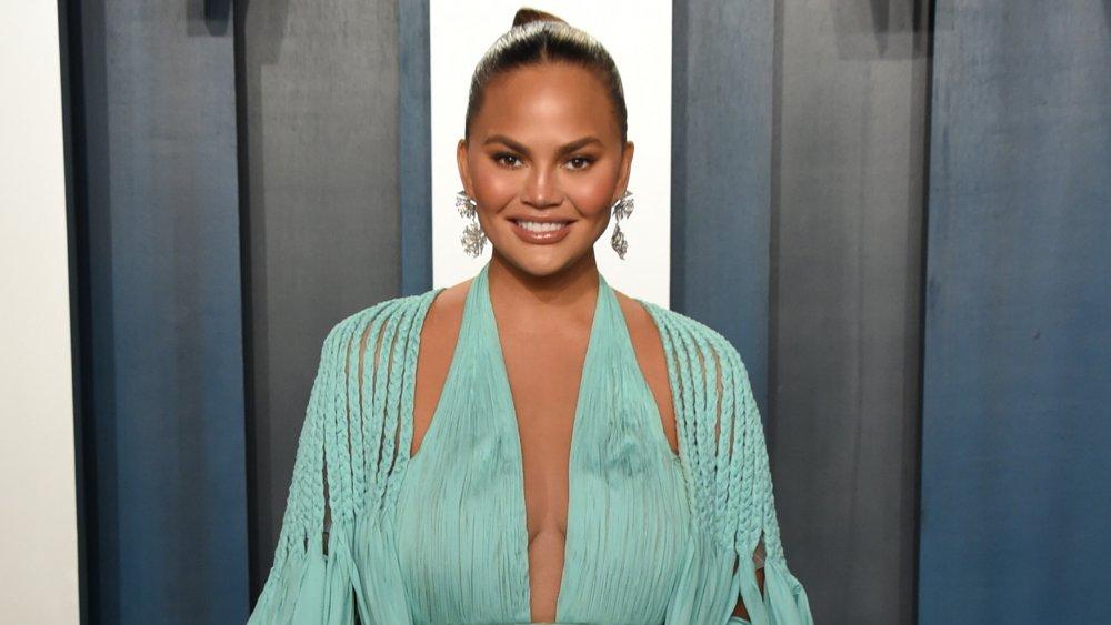 Chrissy Teigen sonriendo mientras posa con un vestido celeste en la Vanity Fair Oscar Party 2020