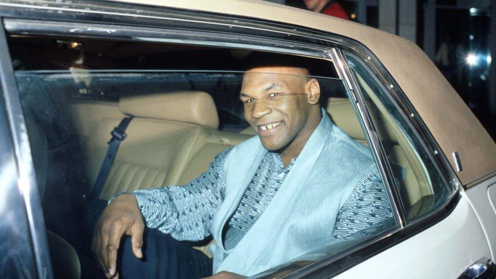 Mike Tyson sonriendo en un auto