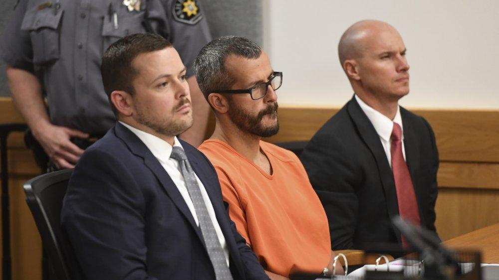 Chris Watts con un mono naranja, sentado con sus abogados en su juicio de 2018