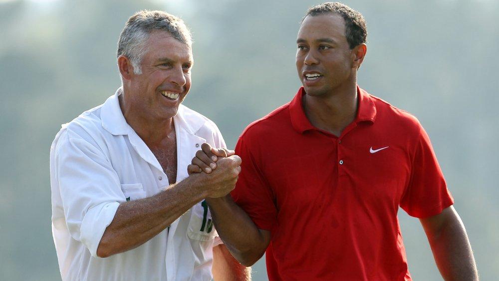 Steve Williams y Tiger Woods se dan la mano y sonríen en el campo de golf