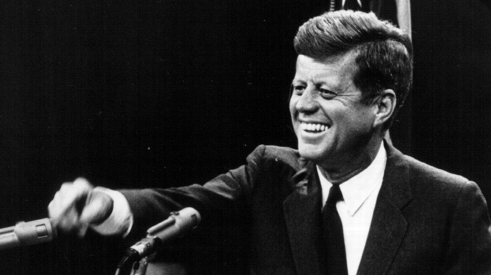 John F. Kennedy riéndose del podio