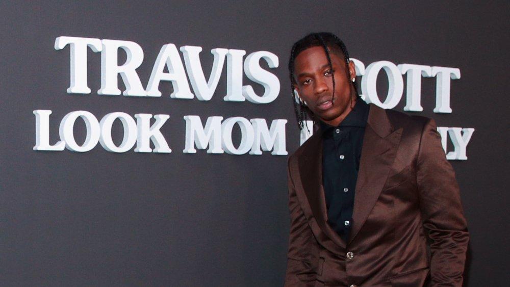 Travis Scott posando frente al título de su álbum