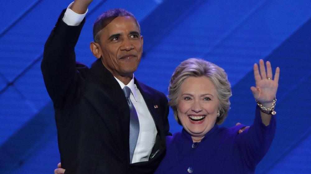 Barack Obama y Hilary Clinton saludando