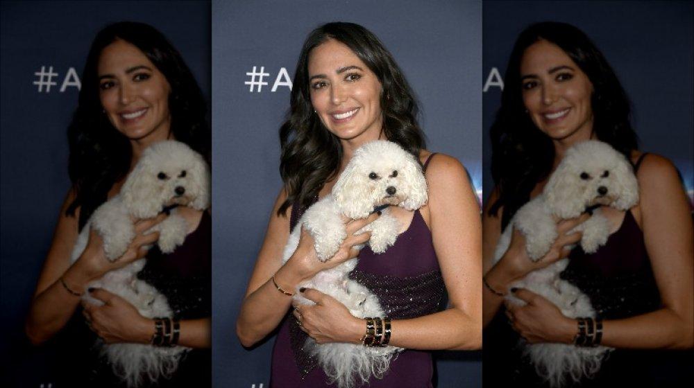 Lauren Silverman sonriendo mientras sostiene a su perro