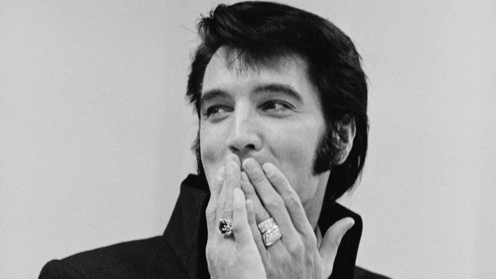 Una foto en blanco y negro de Elvis Presley con anillos y con las patillas tapándose la boca con las manos.