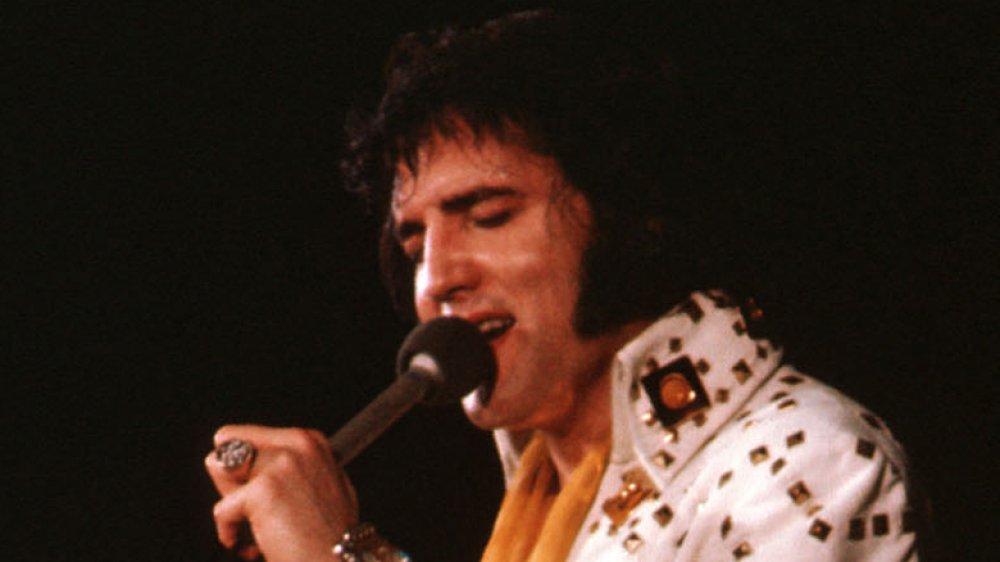 Elvis Presley actúa en 1974 con un mono blanco.