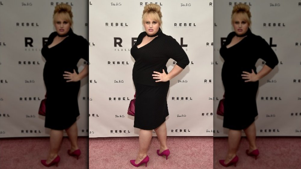Rebel Wilson modelando un vestido negro para su línea de moda