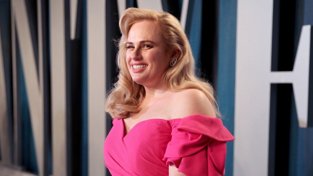 Rebel Wilson sonriendo en vestido rosa