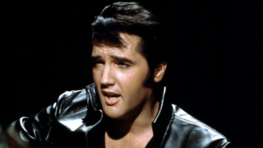 Elvis Presley tocando la guitarra y vistiendo una chaqueta de cuero negra