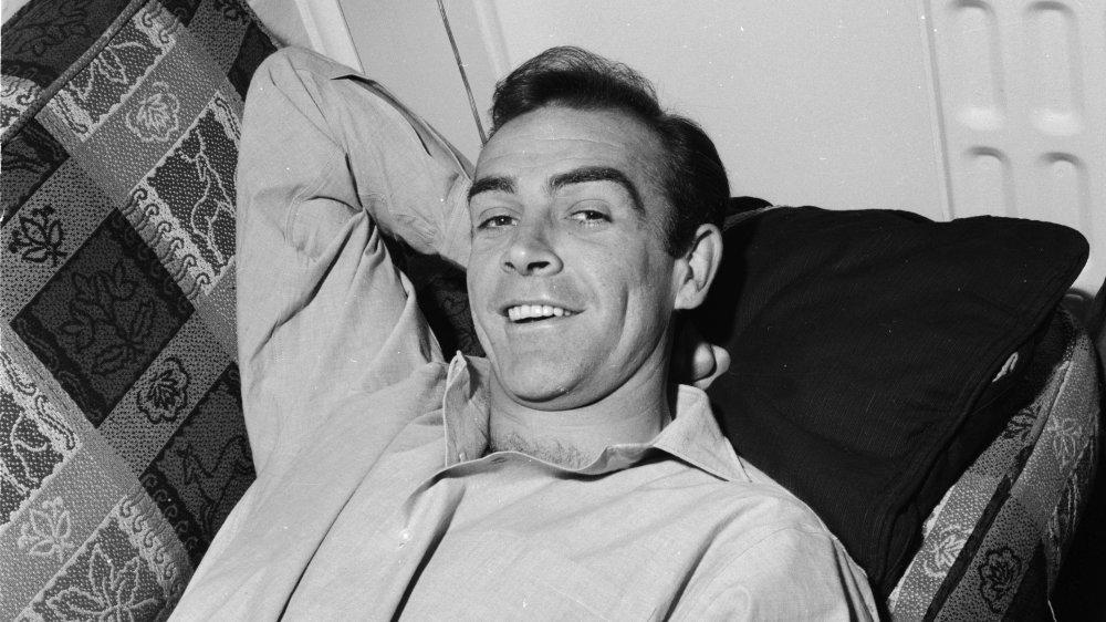 Un joven Sean Connery sonriendo mientras se acuesta en un sofá