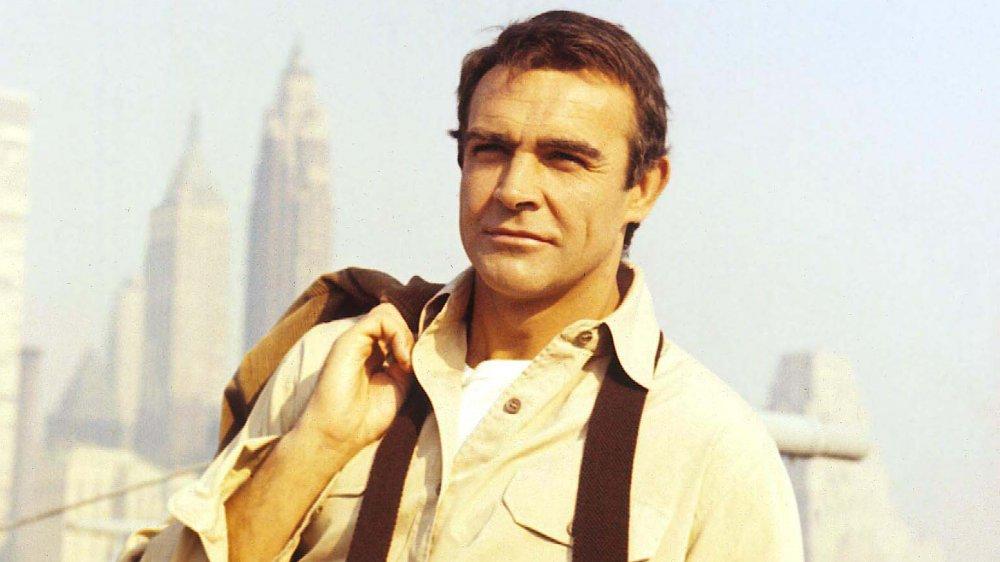 Un joven Sean Connery mirando a lo lejos con su gato colgando del hombro