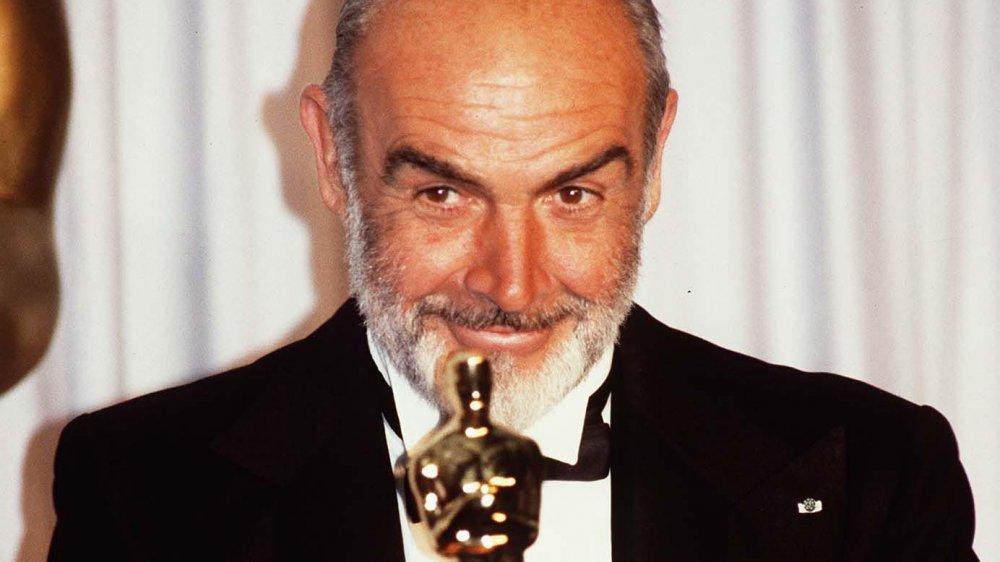 Sean Connery sonriendo mientras sostiene su Oscar