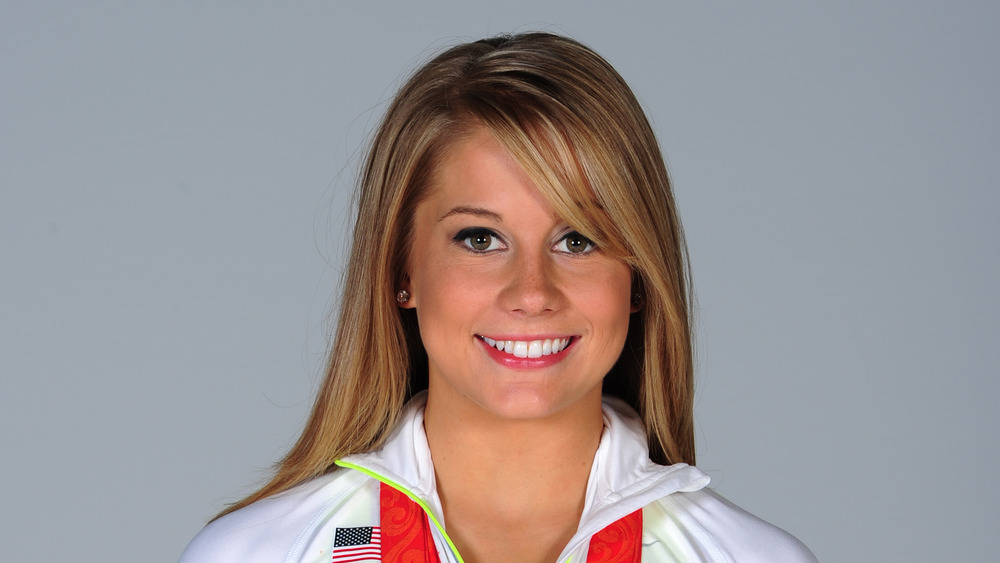 Shawn Johnson en una sesión de fotos con sus medallas