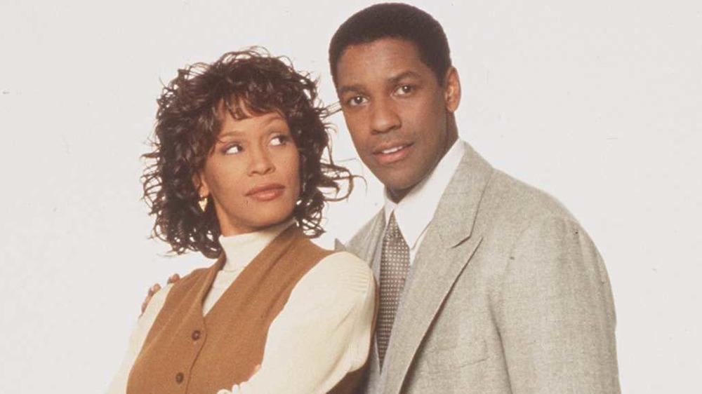 Whitney Houston mirando a Denzel Washington