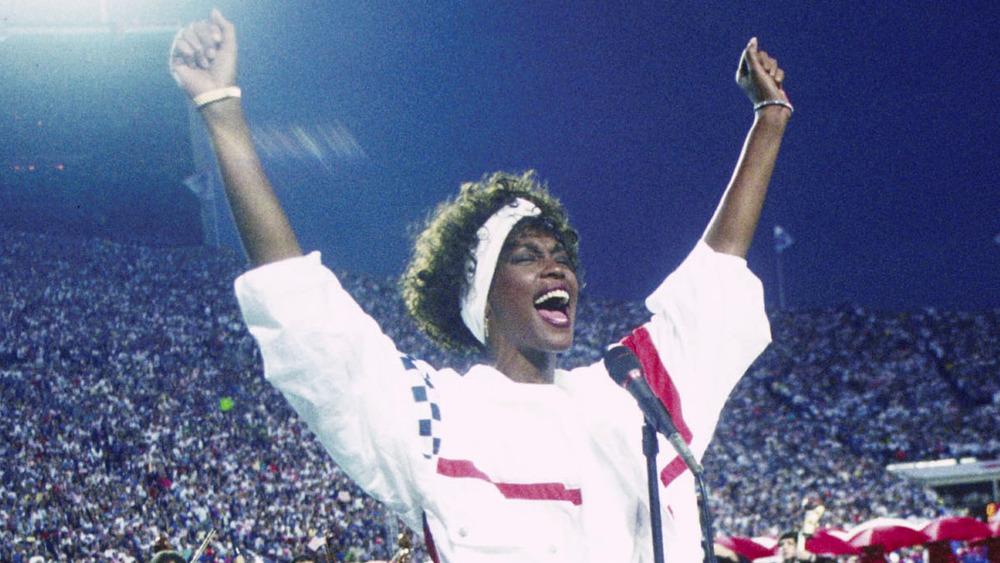 Whitney Houston con las manos arriba, cantando