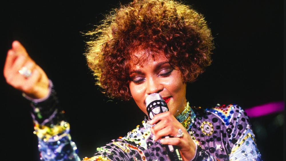 Whitney Houston sosteniendo un micrófono