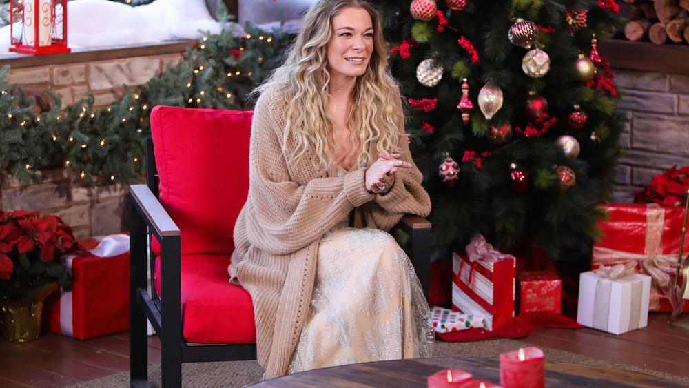 LeAnn Rimes sentada junto al árbol de Navidad
