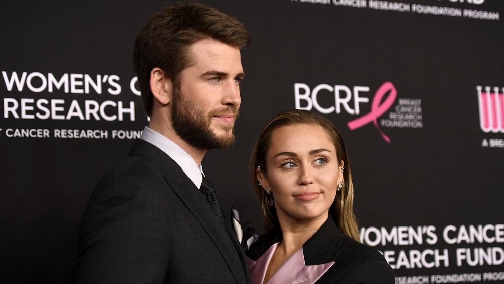 Liam Hemsworth y Miley Cyrus posan en la alfombra roja