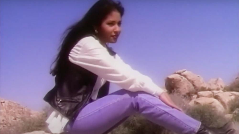 Selena Quintanilla sentada sobre una roca