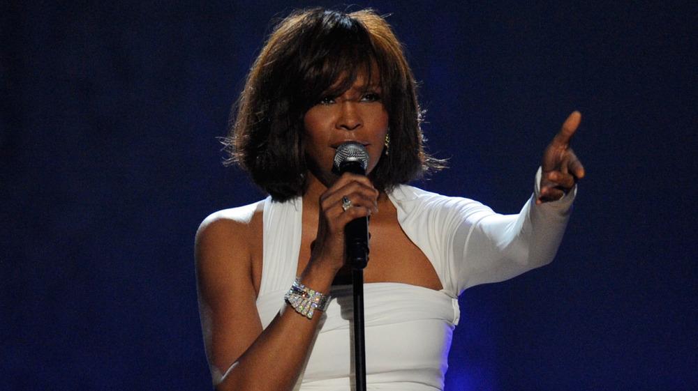 Whitney Houston levantando las manos en el escenario