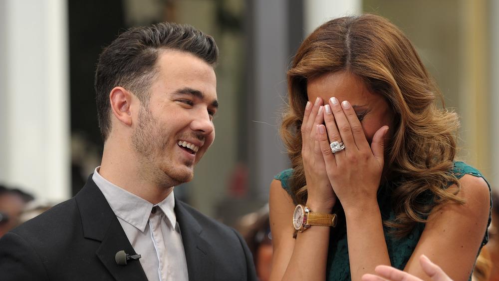 Kevin Jonas sonriendo, Danielle Jonas sorprendida