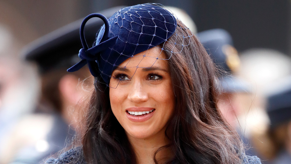 Meghan Markle, la duquesa de Sussex, sonriente y vestida de azul marino