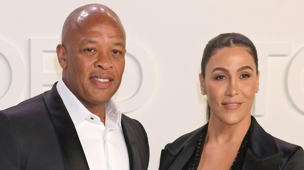 Dr. Dre y Nicole Young posando en la alfombra roja