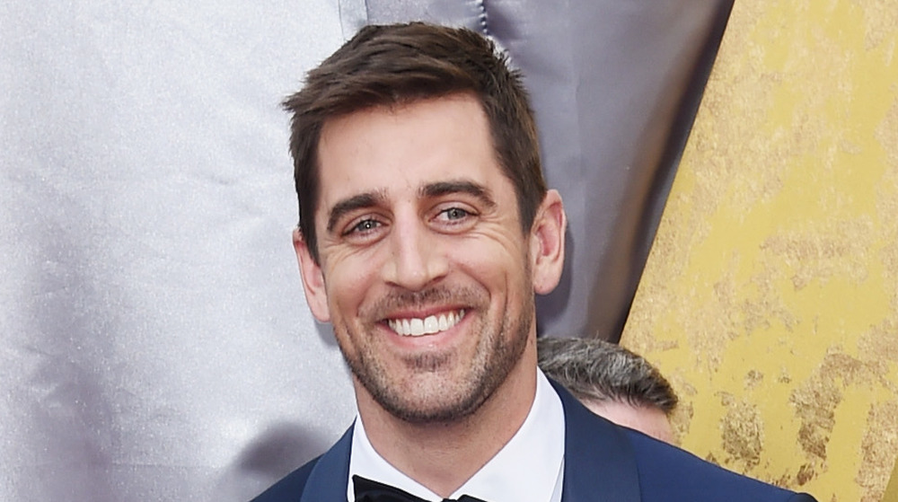 Aaron Rodgers sonríe en la alfombra roja de los Oscar