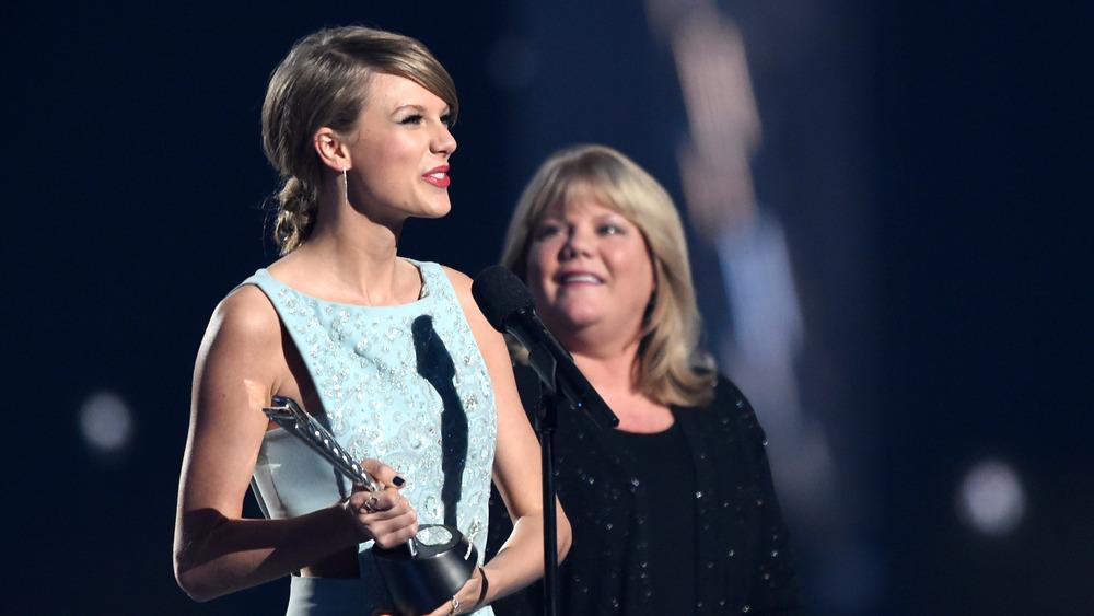 Taylor Swift sostiene una estatua de premio mientras su madre Andrea Swift mira