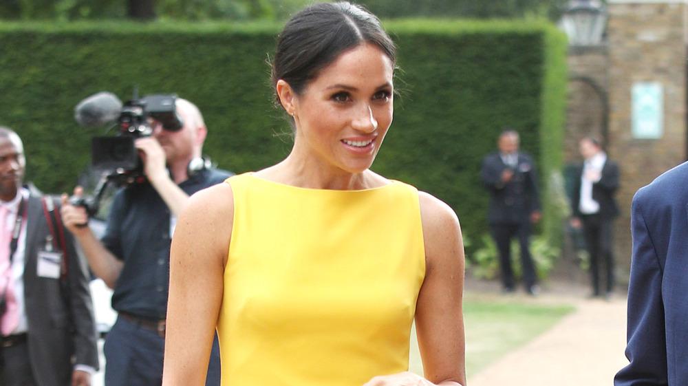 Meghan Markle caminando con un vestido amarillo