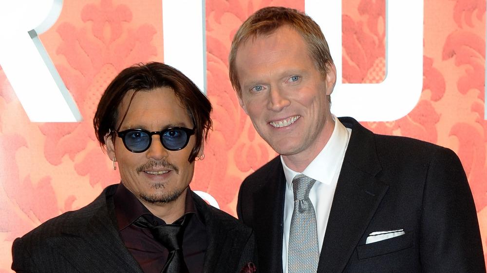 Johnny Depp y Paul Bettany sonriendo en el estreno británico de Mortdecai