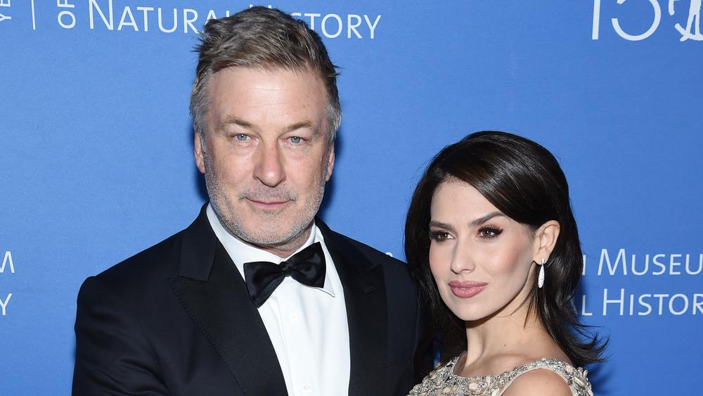 Alec Baldwin posando con su esposa Hilaria Baldwin quien tiene su mano en su pecho