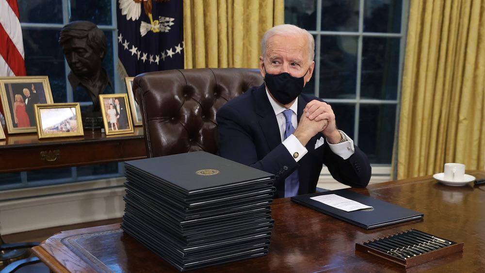 Fotos de la familia Biden están colocadas en un escritorio detrás de Joe Biden preparándose para firmar órdenes.