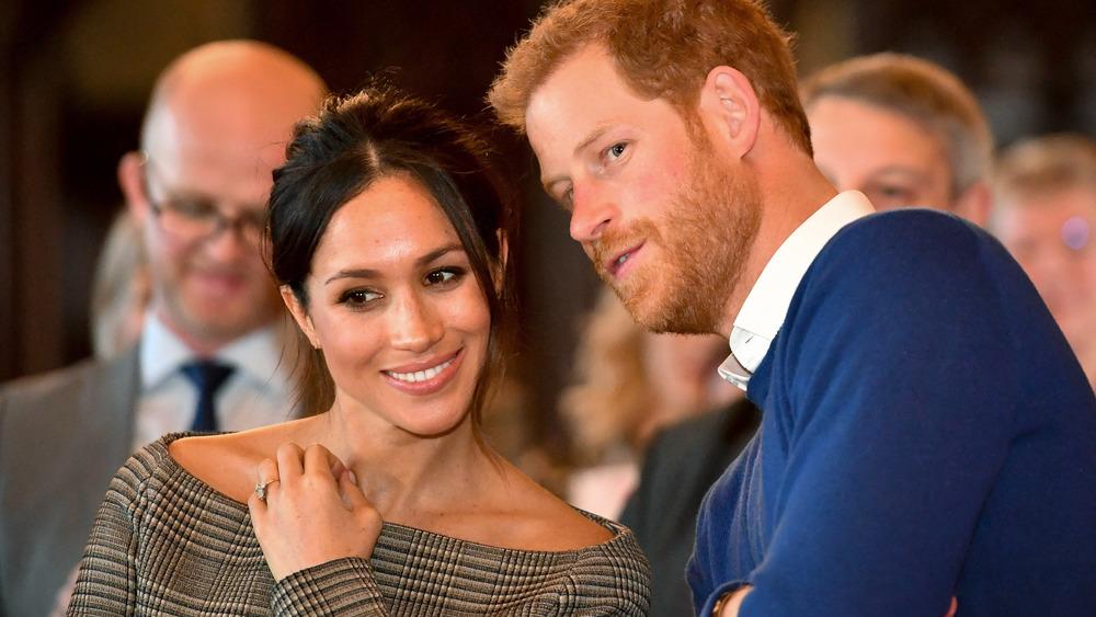 Meghan Markle se ríe con un top sin hombros mientras el príncipe Harry le susurra al oído