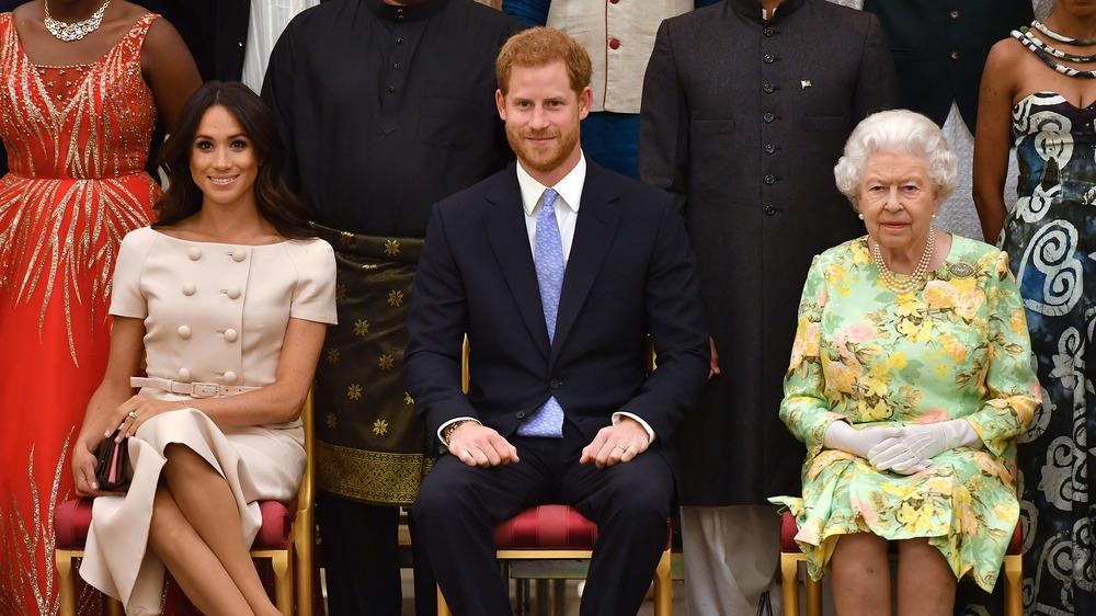 La reina Isabel, el príncipe Harry y Meghan Markle, todos sentados