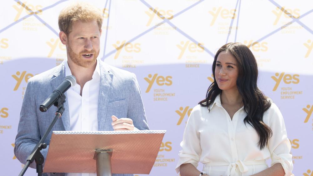 El príncipe Harry hablando en el podio junto a Meghan Markle