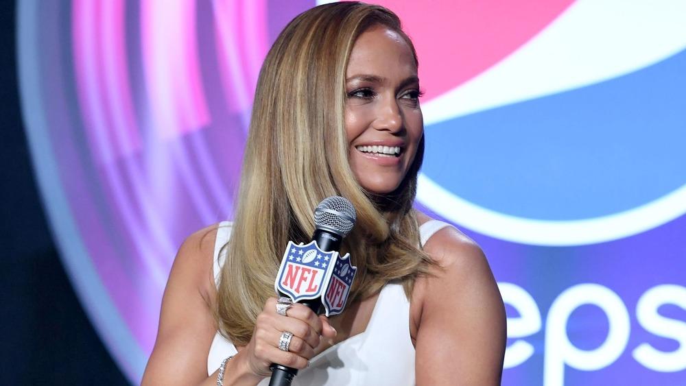 Jennifer Lopez sonriendo con un micrófono