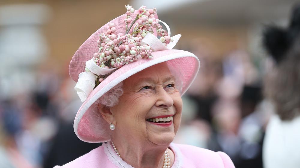 Queen Elizabeth sombrero rosa sonriendo