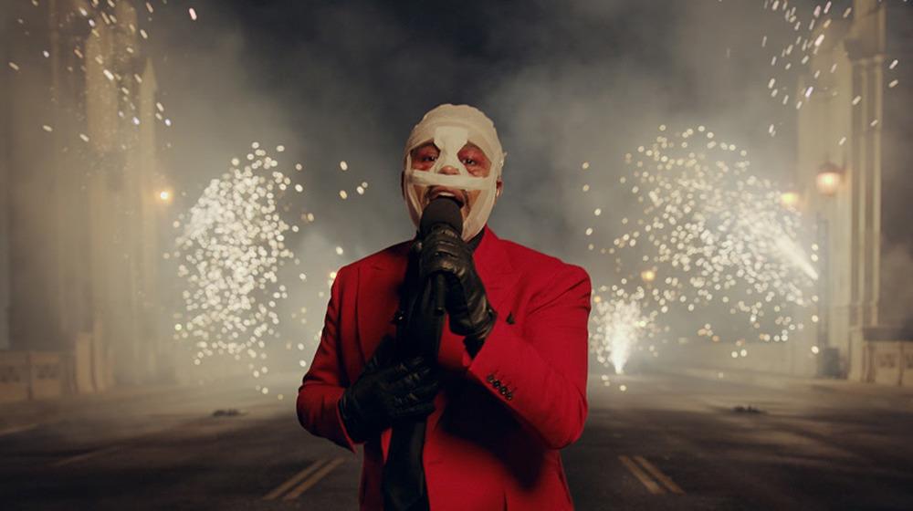 Un The Weeknd enmascarado y vendado actúa frente a un fondo de explosión de fuegos artificiales