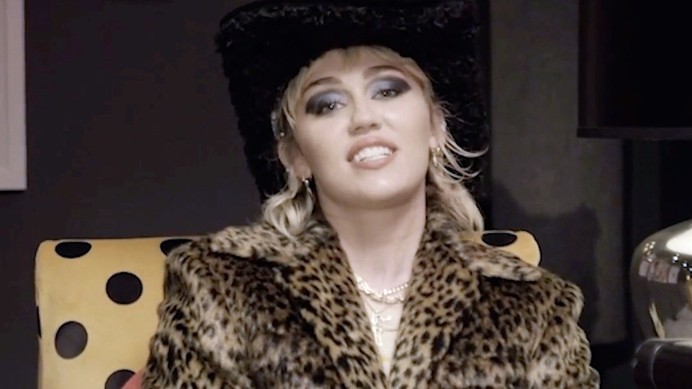 Miley Cyrus se sienta a hablar en una silla junto a una guitarra