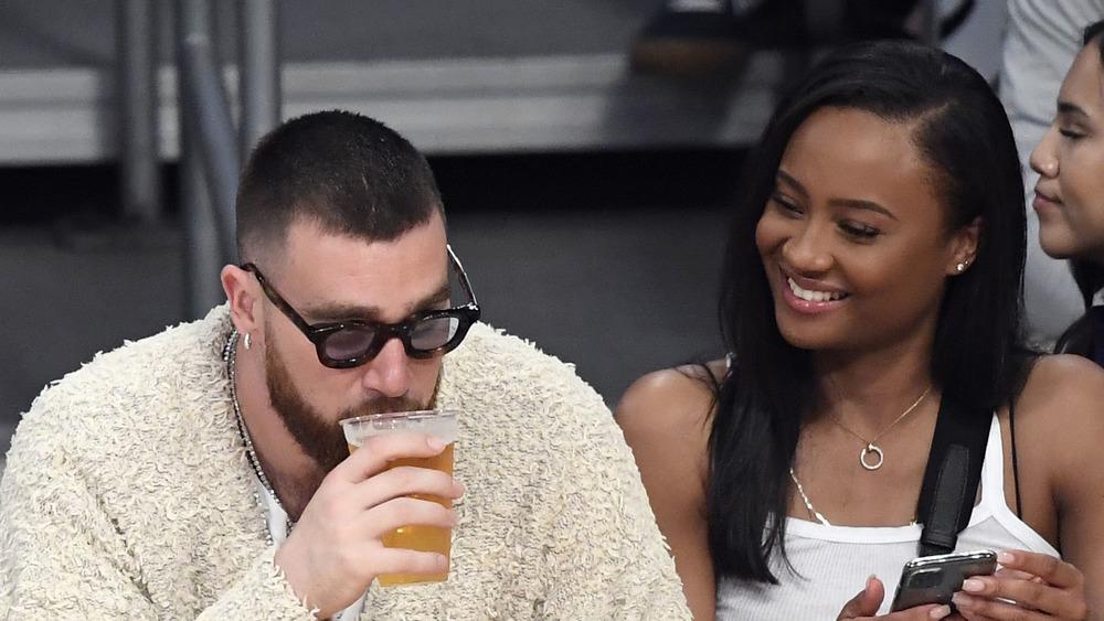Travis Kelce, bebiendo una cerveza, en la cancha en un partido de la NBA, con gafas de sol;  Kayla Nicole, cabello largo suelto, sonriendo a Travis Kelce, camiseta blanca sin mangas, lado de la cancha en un juego de baloncesto