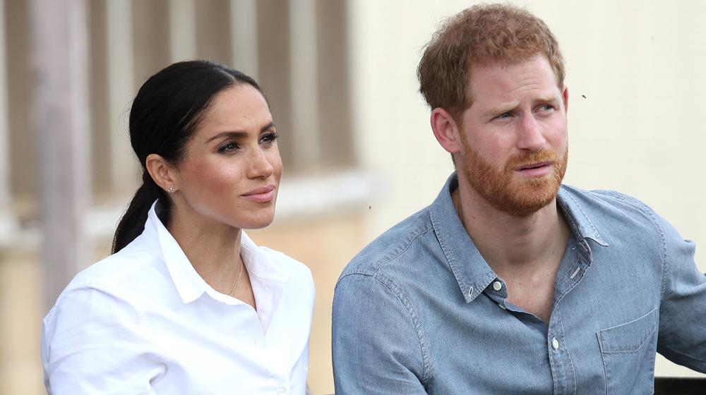 Meghan Markle vestida de blanco se sienta junto al príncipe Harry con una camisa de mezclilla mientras miran pensativamente un evento