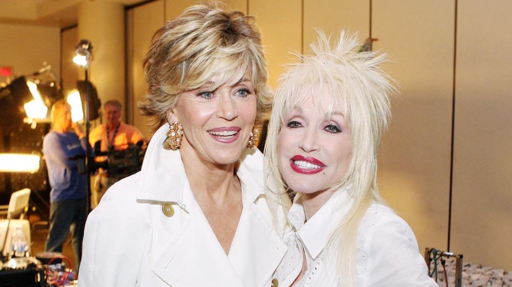 Dolly Parton y Jane Fonda sonriendo vestidas de blanco