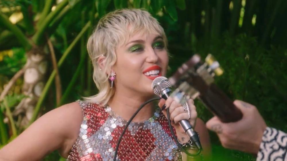Miley Cyrus canta al aire libre con un micrófono con la mano de un guitarrista a la vista