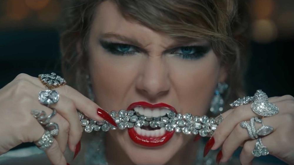 Taylor Swift mordiendo una pieza de joyería de diamantes