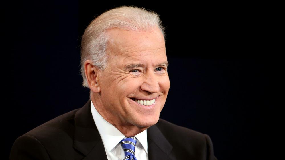 Joe Biden sonríe en el escenario con traje y corbata azul