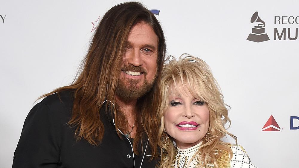 Billy Ray Cyrus y Dolly Parton abrazados en la alfombra roja