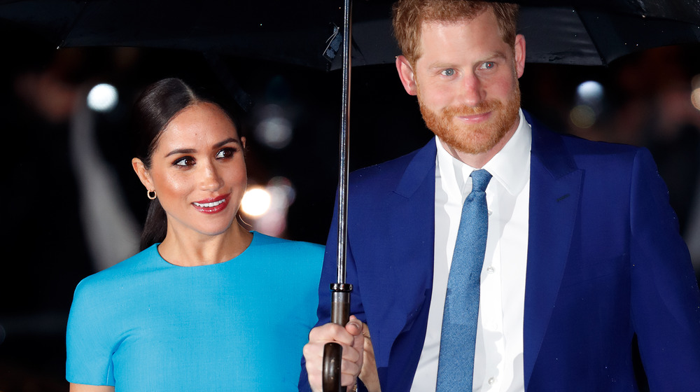 Meghan Markle y el príncipe Harry están bajo una sombrilla en un evento